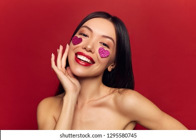 Happy cheerful woman portrait with purple glitter hearts on her face. Valentines day love concept, Beautiful Fashion sexy Girl touching her face