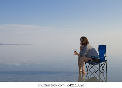 Happy, cheerful woman sitting on fisherman chair and playing with her legs, open arms, reading book, drinking wine, enjoying life on vacation.