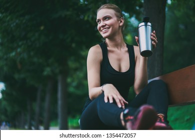 Happy cheerful woman in trendy tracksuit feeling good after morning running holding aluminium bottle with water and smiling, successful slim female jogger looking away and enjoying healthy lifestyle