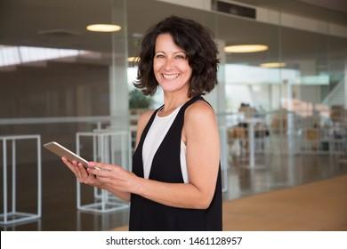 Fröhliche Frau, die Tablette in der Nähe der Glaswand benutzt. Frau im mittleren Alter, die in der Halle steht, digitale Geräte hält und die Kamera lächelt. Kommunikationskonzept