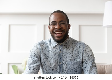 Happy cheerful young black man video calling looking at camera at home, smiling african guy communicate in internet chat recording vlog talking laughing enjoy online conversation, webcam view