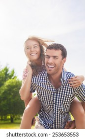 Happy and Cheerful Young Caucasian Couple Piggybacking Outdoors. Green Summer Forest Environment. Vertical Image