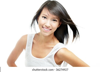 Happy, cheerful young chinese lady with windswept hair and dressed in white, isolated against white.