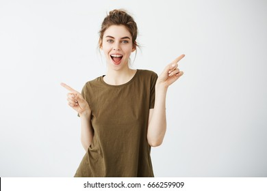 Happy cheerful young girl looking at camera smiling with opened mouth pointing fingers in side over white background.