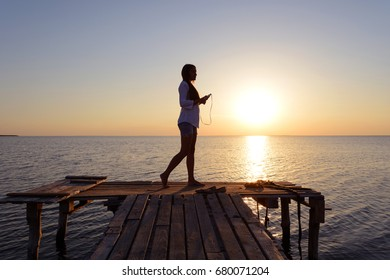 Happy cheerful young girl in a white shirt listening to music on headphones and dancing on the dock by the sea at sunset