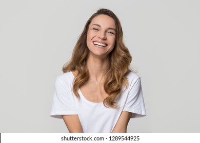 Happy cheerful young woman with beautiful face, teeth and hair laughing looking at camera on white light background, smiling pretty girl model having fun isolated on blank grey studio wall, portrait
