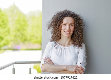 Happy cheerful young woman with curly hair and positive atitude, looking at camera with joyful and charming smile.
