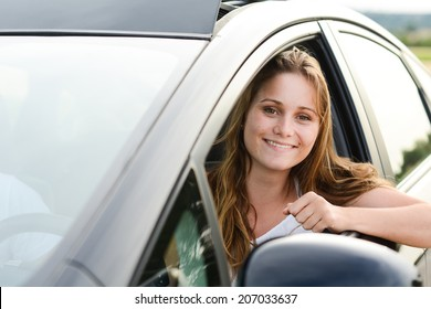 happy cheerful young woman driving her brand new car with new drivers license