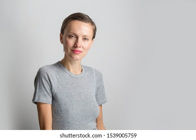 Happy cheerful young woman with short hair, natural makeup over light white grey background. Indoor portrait of beautiful brunette young  woman