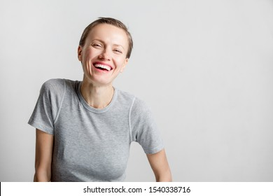 Happy cheerful young woman with short hair, natural makeup over light white grey background. Indoor portrait of beautiful brunette young woman smiling cheerfully