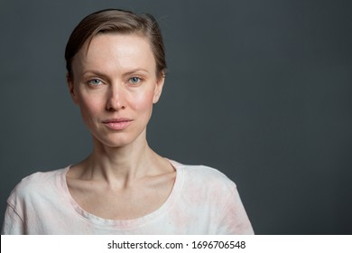 Happy cheerful young woman with short hair, natural makeup over grey background. Indoor portrait of beautiful brunette young woman