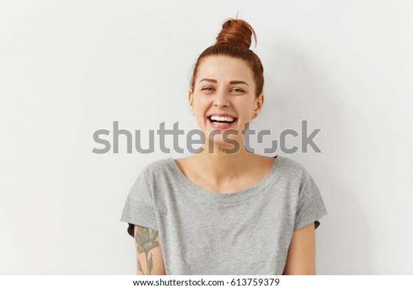 Fröhliche junge Frau, die ihr rotes Haar trug und sich über positive Neuigkeiten oder Geburtstagsgeschenk freut, die Kamera mit einem fröhlichen und charmanten Lächeln anschaut. Ingwer Studentenmädchen entspannen im Haus nach der Uni