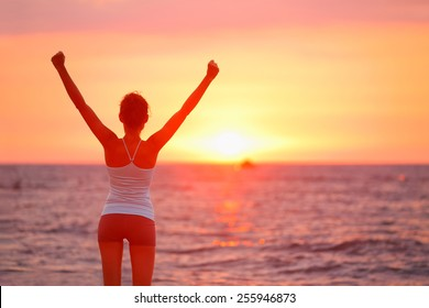 Happy cheering celebrating success woman at beautiful beach sunset. Fitness girl enjoying view with arms raised up towards the sky. Happy free freedom sport concept image outdoors.