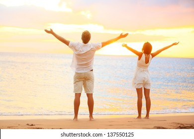 Happy cheering couple enjoying sunset at beach with arms raised up in joyful elated happiness. Happiness concept with young joyous couple, Caucasian man and Asian woman.