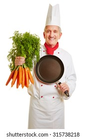 Happy chef cook in workwear with a pan and bunch of carrots