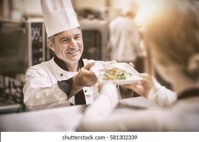 Happy chef handing dinner dish to waitress in kitchen at order station