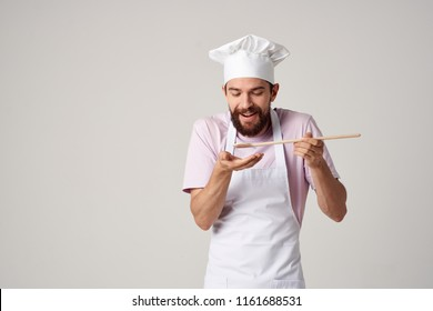 happy chef looks at a wooden spoon, try a dish