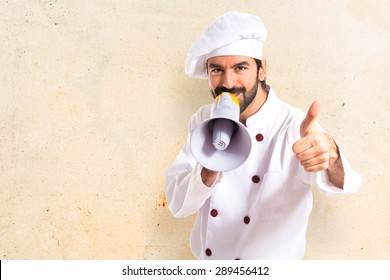 Happy chef shouting by megaphone