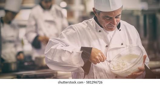 Happy chef whisking cream in kitchen