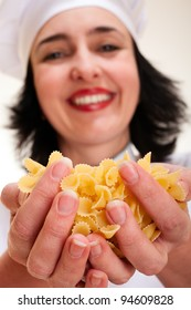 Happy chef woman holding macaroni handful in hands