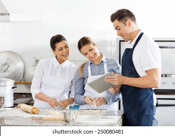 Happy chefs checking recipe on digital tablet while preparing pasta in commercial kitchen