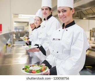 Happy Chef's showing their salads in the kitchen