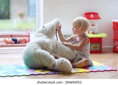 Happy child, adorable blonde toddler girl, playing doctor game with her teddy bear sitting comfortable on the floor in playroom at home, school or kindergarten