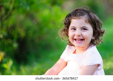 Happy child, an adorable little girl laughing in the park on a nice spring day