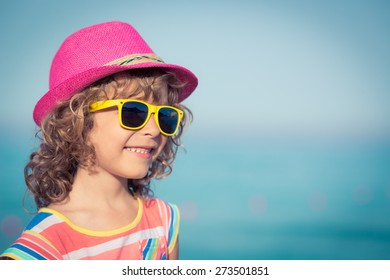 Happy child against sea and sky background. Summer vacation and travel concept