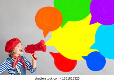 Happy child artist shouting by loudspeaker. Imagination and childhood dream concept