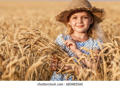 Happy child in autumn wheat field. Beautiful girl with white hair in a straw hat with ripe wheat in hands