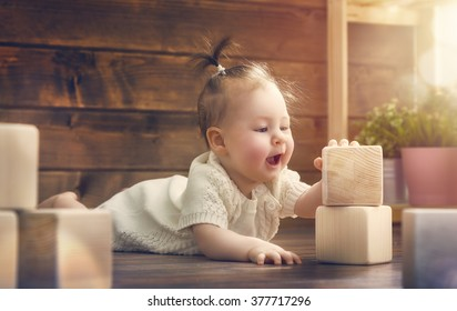 happy child  baby girl playing with blocks and having fun.