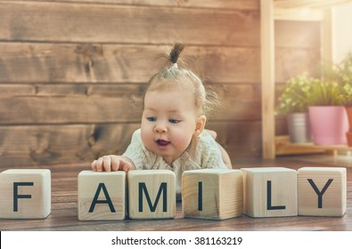 Happy child baby girl playing with blocks and having fun. Blocks have letters. The child puts the word Family.