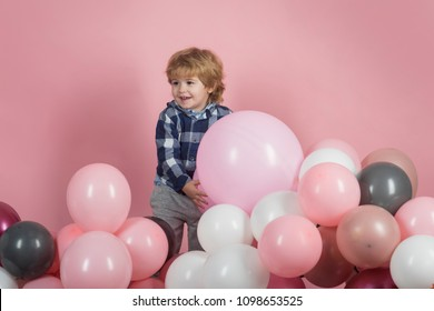 Happy child with balloons. Boy with toys on a pink background. A boy in a blue shirt on a pink background. Attractive little man is playing in the garden. Happy childhood