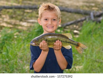 Happy child with a big fish he caught next to a pond