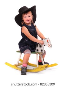 Happy child in big hat on a rocking horse.
