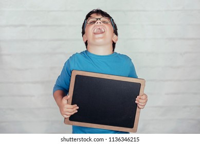 happy child with a blackboard on brick background
