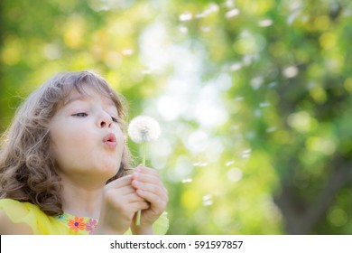 Happy child blowing dandelion flower outdoors. Girl having fun in spring park. Blurred green background. Dream and imagination concept