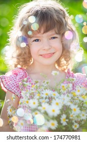 Happy child with bouquet of daisy flowers against green background. Spring family holiday concept. Mother`s day