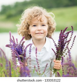 Happy child with bouquet of flowers playing in spring field. Mothers day concept