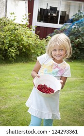 Happy child with a bowl of freshly picked berries