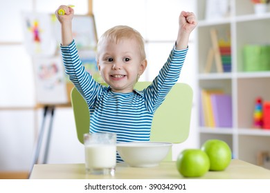 Happy child boy eating breakfast with hands up