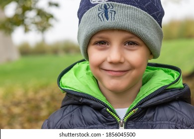 Happy child boy with hat and winter jacket is posing on an autumn day. Photography in the woods with beautiful bokeh.