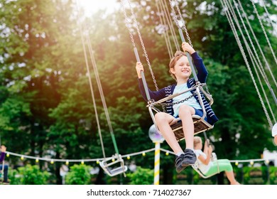 Happy child boy having fun in amusement park. Taking a ride on chain carousel.