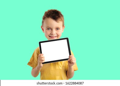 Happy child boy  holding a tablet ipade for your information on the Aqua Menthe background