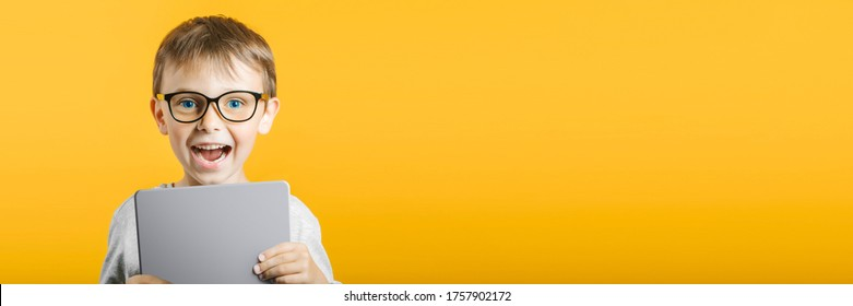 Happy child boy  holding a tablet  for your information on the yellow background