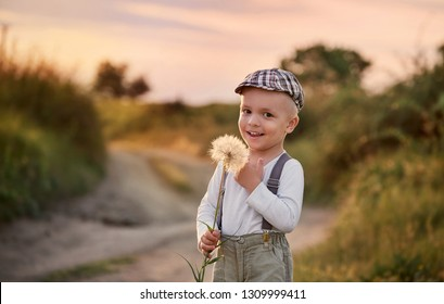 Happy child boy on nature spring,field,meadow,sunlight. Beautiful smiling baby holding big dandelion flower in his hands. Summer portrait little kid wearing fashionable retro clothes, cap,suspenders.