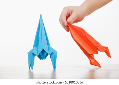 Happy child boy playing with handmade origami paper rocket