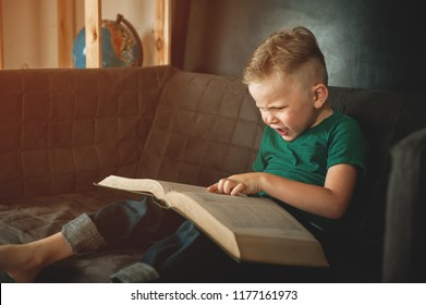 Happy child boy reading a book while sitting at sofa at home. Preschool child reading a magic book in the dark interior. Toddler boy is studing alone. Back to school