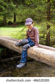 Happy child boy sitting on wooden bridge over stream or creek  or river in forest in nature.